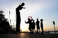 A stilt walker entertains as the sun sets over Lake Mendota near the University of Wisconsin campus in Madison, Wisconsin.