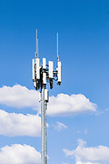 3 sector cellular telecom communications panel antenna array for the mobile telephone system on a cellsite pole tower against cumulus clouds. <br /> <br /> Editions:- Open Edition Print / Stock Image