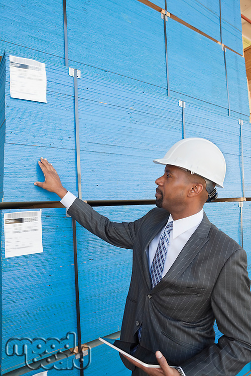 African American male contractor inspecting wooden planks while holding tablet PC
