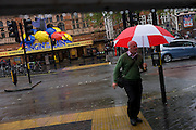 On a rainy day, a pedestrian hurries past during a shower outside where the musical Singing in the Rain is playing.
