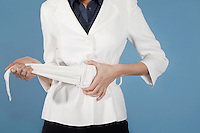 Businesswoman adjusting belt mid section