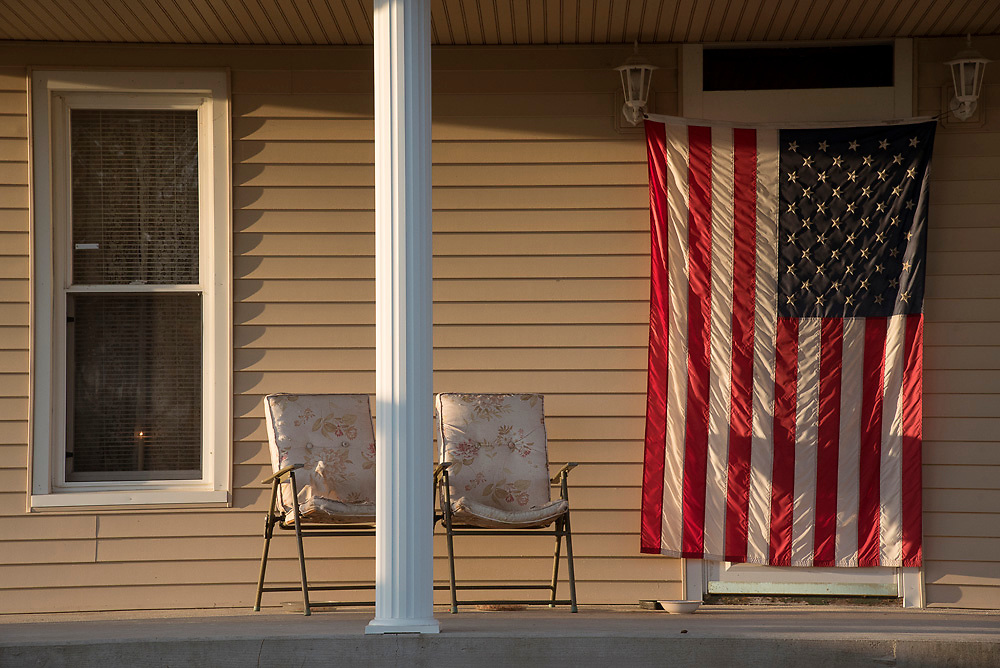An American flag hangs over the front door of Jane Linscott's home where her parents used to live. A neighbor hung the flag to honor Jane's father when he passed away, and she has yet to take it down.