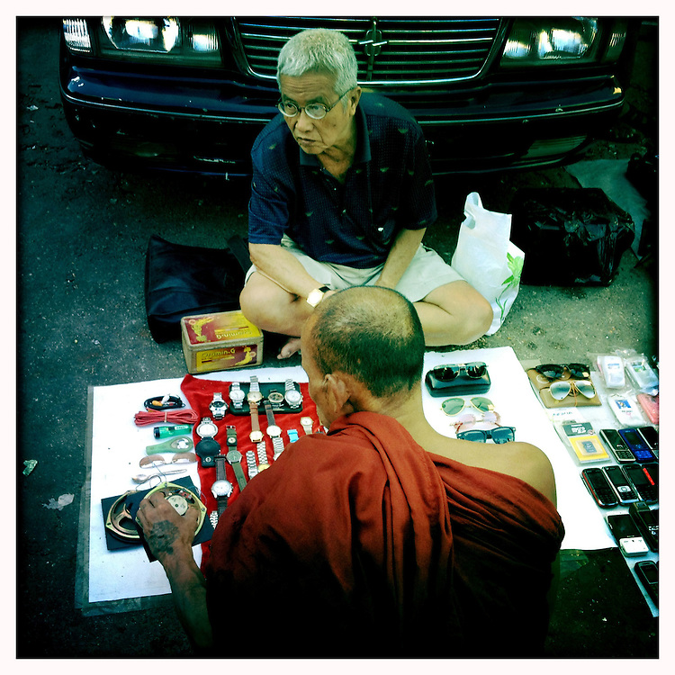 A monk checks out time-pieces at a street market in Yangon (Rangoon) Myanmar (Burma) January 2012