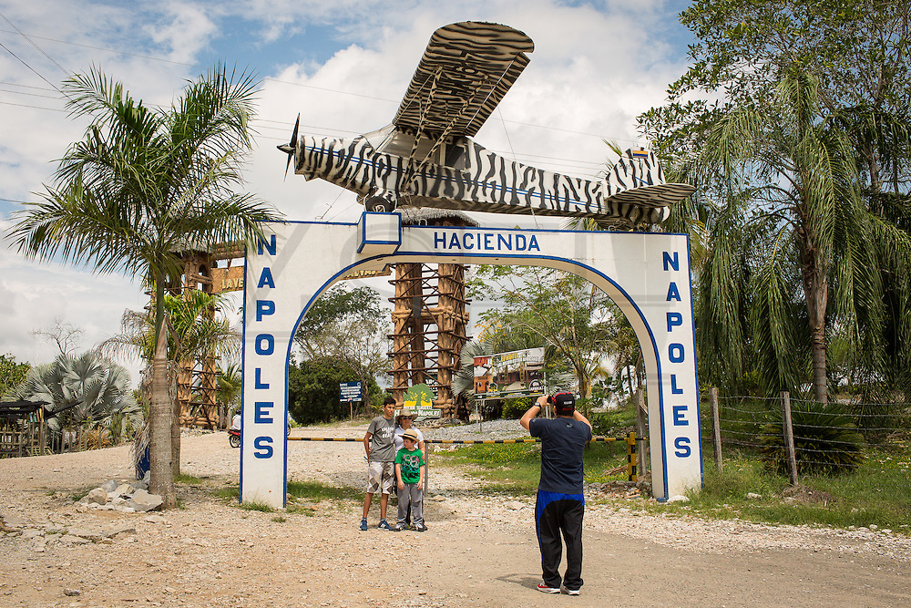2015/11/21 - Puerto Triunfo, Colombia: Tourists take a photo at the front gate of Hacienda Nápoles. The Hacienda Nápoles was a 20sq kilometer property own by drug lord Pablo Escobar. In its splendor, the property had its own private airport, bull arena, kart racing circuit and even a private zoo that included many kinds of animals from different continents such as giraffes, ostriches, elephants, hippopotamuses, antelope, and exotic birds. After the death of Pablo Escobar in 1993, the family went into a legal struggle with the Colombian government over the property. Nowadays it is an leisure park, where most of Escobar presence disappeared. (Eduardo Leal)