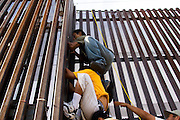Migrants work together to illegally climb a border fence into the United States from Mexicali, Mexico on Friday, April 14, 2006.<br />