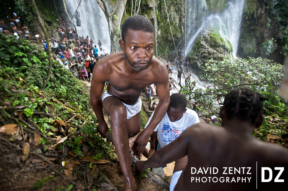 Pilgrims climb up a steep dirt wall to a cliff overlooking the waterfall at Saut D'eau in central Haiti during an annual voodoo pilgrimmage held there each July.