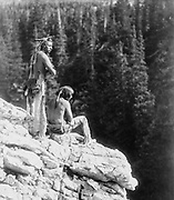 Two Native Americans looking over the edge of a cliff, c1912.  Photograph by Roland W. Reed (1864-1934).
