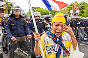 24 NOVEMBER 2012 - BANGKOK, THAILAND: A woman professes her love of the monarchy and Bhumibol Adulyadej, the King of Thailand, in front of riot police during a large anti government, pro-monarchy, protest  on November 24, 2012 in Bangkok, Thailand. The Siam Pitak group, which sponsored the protest, cited alleged government corruption and anti-monarchist elements within the ruling party as grounds for the protest. Police used tear gas and baton charges againt protesters.       PHOTO BY JACK KURTZ