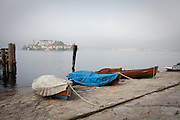 Boats docked on a foggy day, Orta San Giulio, Piedmont, Italy.