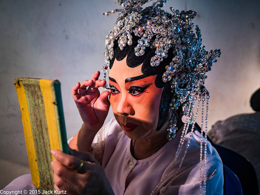 15 OCTOBER 2015 - BANGKOK, THAILAND: A Chinese opera performer puts on her eyelashes before performing at the Vegetarian Festival at the Joe Sue Kung Shrine in the Talat Noi neighborhood of Bangkok. The Vegetarian Festival is celebrated throughout Thailand. It is the Thai version of the The Nine Emperor Gods Festival, a nine-day Taoist celebration beginning on the eve of 9th lunar month of the Chinese calendar. During a period of nine days, those who are participating in the festival dress all in white and abstain from eating meat, poultry, seafood, and dairy products. Vendors and proprietors of restaurants indicate that vegetarian food is for sale by putting a yellow flag out with Thai characters for meatless written on it in red. The shrine is famous for the Chinese opera it hosts during the Vegetarian Festival. The operas are free.    PHOTO BY JACK KURTZ