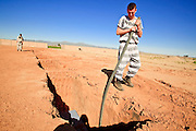 "18 MARCH 2010 - SURPRISE, AZ:  County inmate Robert Henderson straightens coffins after they've been lowered into the graves in White Tanks Cemetery on Camelback Rd. in an unincorporated part of the county near Surprise. The county spent about $2.5 million to inter indigent people in what is Maricopa County's ""potters field."" About 3,000 people, children and adults, are buried in the dusty field west of Phoenix.     PHOTO BY JACK KURTZ"