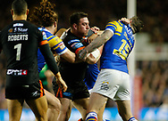 Brett Delaney (R) and Anthony Mullally (L) of Leeds Rhinos tackle Grant Millington (C) of Castleford Tigers during the Betfred Super League match at Elland Road, Leeds<br /> Picture by Stephen Gaunt/Focus Images Ltd +447904 833202<br /> 23/03/2018