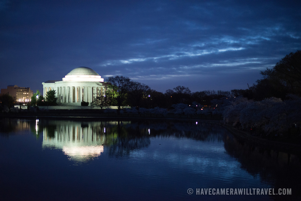 The Jefferson Memorial is lit up before dawn and reflected on the still waters of the Tidal Basin in Washington DC.
