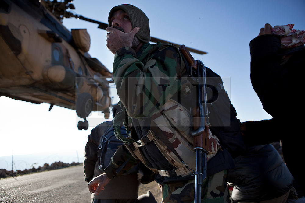 © Licensed to London News Pictures. 11/12/2014. Sinjar Mountains, Iraq. A Yazidi fighter holds his hat on to keep it from blowing off in the downdraft created by an Iraqi Air Force Mi-17 Hip helicopter during a mission to drop supplies and evacuate families on the top of Mount Sinjar.<br /> <br /> Although a well publicised exodus of Yazidi refugees took place from Mount Sinjar in August 2014 many still remain on top of the 75 km long ridge-line, with estimates varying from 2000-8000 people, after a corridor kept open by Syrian-Kurdish YPG fighters collapsed during an Islamic State offensive. The mountain is now surrounded on all sides with winter closing in, the only chance of escape or supply being by Iraqi Air Force helicopters. Photo credit: Matt Cetti-Roberts/LNP
