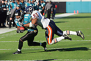 JACKSONVILLE, FL - DECEMBER 12:  Wide receiver Troy Edwards #16 (caught 4 passes for 30 yards) of the Jacksonville Jaguars looks for extra yardage with linebacker Lance Briggs #55 of the Chicago Bears on his back on December 12, 2004 at Alltel Stadium in Jacksonville, Florida. The Jags defeated the Bears 22-3. ©Paul Anthony Spinelli *** Local Caption *** Troy Edwards;Lance Briggs