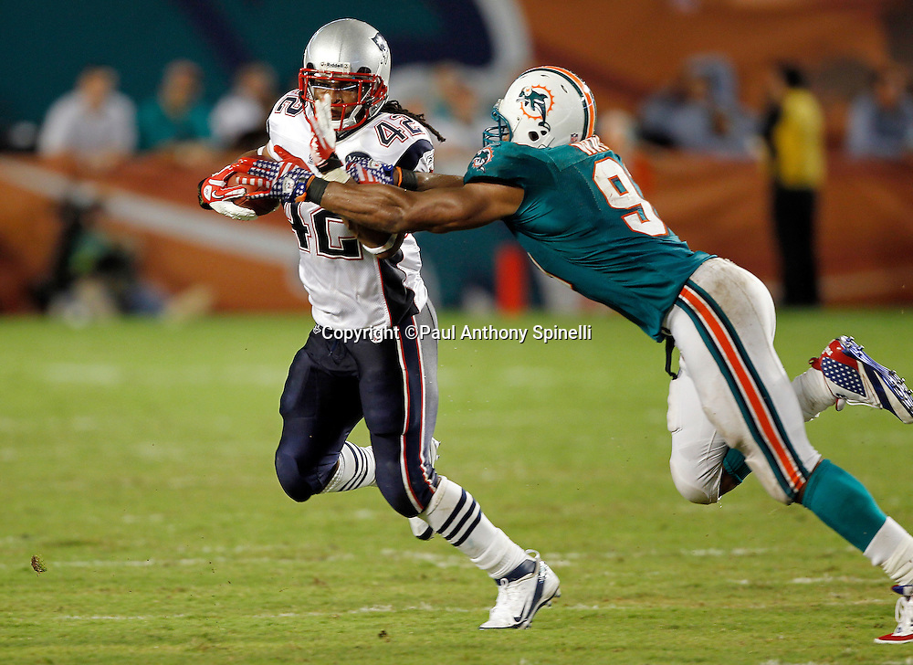 New England Patriots running back BenJarvus Green-Ellis (42) runs the ball while avoiding a tackle attempt by Miami Dolphins linebacker Cameron Wake (91) during the NFL week 1 football game against the Miami Dolphins on Monday, September 12, 2011 in Miami Gardens, Florida. The Patriots won the game 38-24. ©Paul Anthony Spinelli