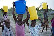 Camp de re?fugie?s pre?s de Govuro..Mozambique, sud-est de l'Afrique. Des enfants transportent des bidons d'eau potable dans un camp de de?place?s, victimes d'une inondation re?cente. A? la brunante, la lumie?re devient douce et bleute?e.