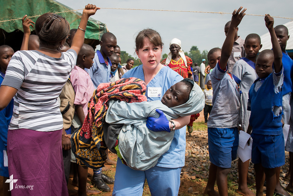 Dr. Katie Butler, a critical care surgeon from Boxford, Mass., attending Our Savior Lutheran Church in Topsfield, Mass., carries a boy suffering from a severe wound to a bus for transport to the hospital during the Mercy Medical Team clinic Friday, June 13, 2014, at the Luanda Doho Primary School in Kakmega County, Kenya. LCMS Communications/Erik M. Lunsford