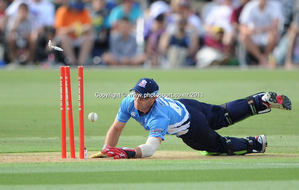 Auckland wicketkeeper Gareth Hopkins dives in an attempted run out of Corey Anderson during the HRV Twenty20 Cricket match between the Auckland Aces and Northern Knights at Colin Maiden Oval in Auckland on Monday 26 December 2011. Photo: Andrew Cornaga/Photosport.co.nz