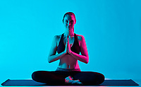 one caucasian woman exercising Padmasana Lotus position yoga exercices  in silhouette studio isolated on blue background