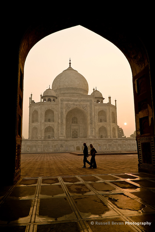 A couple walk round the Taj Mahal just after sunrise in Agra, Uttar Pradesh, India