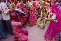 Inde, Uttar Pradesh, fete de Holi, Fete de la couleur et du printemps qui celebre les amours de Krishna et Radha. Les femmes des villages armées d'un long baton de bambou ont le jour de Holi le droit de frapper les hommes qui ont juste le droit de se proteger.  // India, Uttar Pradesh, Holi festival, color and spring festival, celebrate the love between Krishna and Radha. Hundreds of women wear bamboo stick and during Holi, the village women have the freedom to hit men who are only allowed to protect themselves.