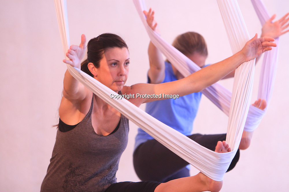 Melinda Finch, left, and Lauren Casey participate in an Aerial Yoga class at Salty Dog Yoga Sunday April 6, 2014 in Carolina Beach, N.C. (Jason A. Frizzelle)