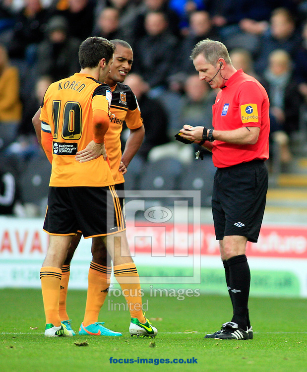 Picture by Richard Gould/Focus Images Ltd +44 7855 403186.03/11/2012.Jay Simpson (2nd L) of Hull City receives a yellow card off Ref Heywood as Robert Koren(C) remonstrates  during the npower Championship match at the KC Stadium, Kingston upon Hull.