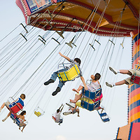 Group of kids riding the spinning swing at an amusement park, Navy Pier, Chicago, IL