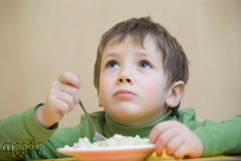 Portrait young boy gazing upwards  while eating