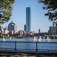 Boston skyline with sailboats on the Charles River. Includes John Hancock Tower and a railing along the Dr. Paul Dudley White Bike Path. Boston Massachusetts is a major city in the Eastern United States of America.