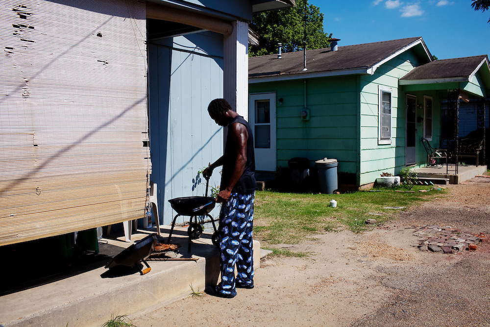 A man prepares for fourth of July celebrations by grilling ribs in front of his family's home the Baptist Town neighborhood of Greenwood, Mississippi on Sunday, July 4, 2010.