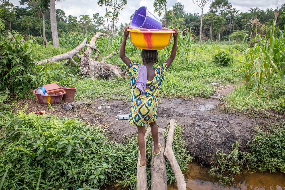 A young girl carries a colorful bucket on her head in Ganta Liberia