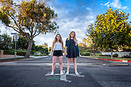 "Natalie Schoemann and Katie Duke hold hands at the intersection of Via de la Paz and Friends Street in the idyllic neighborhood near ""the Bluffs"" in Pacific Palisades, California."
