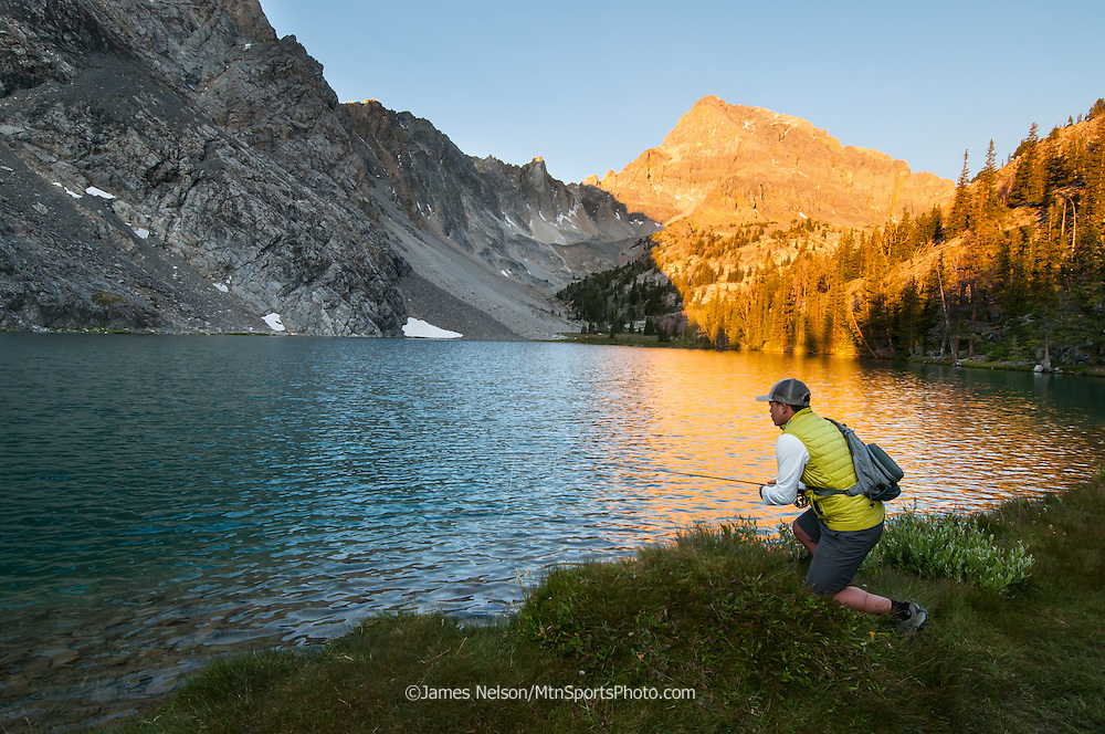 An angler fly fishes for trout on an alpine lake in the Lost River Range in Idaho.