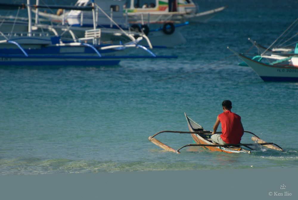 The red-shirted boy in his banca, Boracay, Philippines