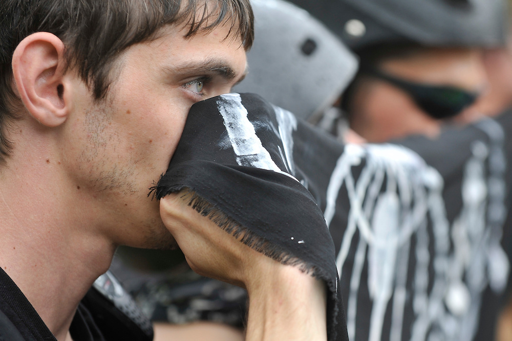 A Black Bloc protestor shields his face during a march against the Republican National Convention, Monday, August 27, 2012 in Tampa, FL. Hundreds of protestors marched through the streets of Tampa to a public viewing area near the Tampa Bay Times Forum, site of the Republican National Convention. (AP Photo/Chris Post)