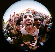 A man sticking his tongue out in a large cheering crowd at a concert, Western Australia, 1990's