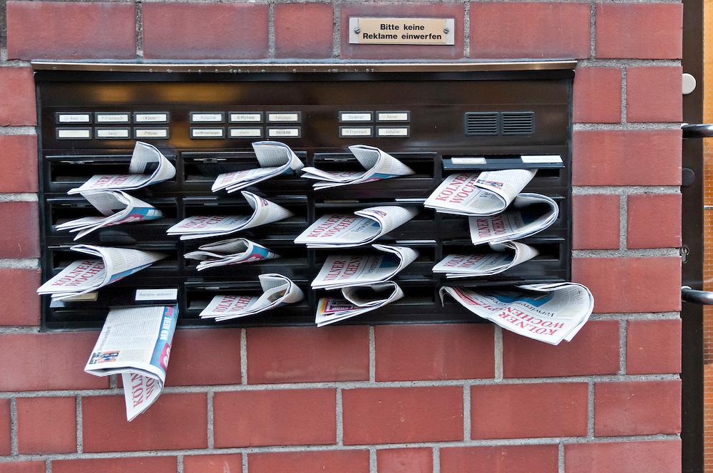 DEU,Deutschland,NRW,Nordrhein-Westfalen,Koeln,Köln, Der Kölner Wochenspiegel eine gratis Werbezeitung steckt in sechzehn Briefkästen an einer Häuserfront. Darüber das Messingschild Bitte keine Reklame einwerfen |  Germany,Cologne,  |