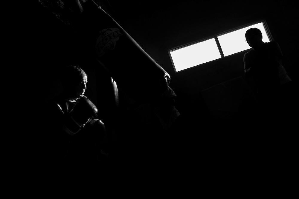 """Luis Lazarte (izquierda) golpea una bolsa de entrenamiento bajo la atenta mirada y supervisión de su entrenador Fernando Sosa (derecha), Mar del Plata, Provincia de Bs. As., Argentina.<br /> Fernando """"Maravilla"""" Sosa, fue campeón argentino y latinoamericano en la categoría """"Pluma"""" (featherweight). Su intensa y elogiada carrera como boxeador profesional, sin haber sido noqueado en ninguna ocasión, se vio obligada a finalizar en el año 1986 al sufrir un segundo desprendimiento de retina y perder por completo la visión del ojo derecho. El 23 de junio de ese año, Sosa, tenía que enfrentarse a Barry McGuigan en la ciudad de Las Vegas, USA, por el titulo mundial de boxing de la categoría """"Pluma"""", pero su lesión lo dejó fuera de competencia.<br /> En la actualidad, Sosa,  es el entrenador del ex campeón mundial Luis Lazarte y uno de los entrenadores más importantes de Argentina en base a su extensa experiencia como boxeador."""