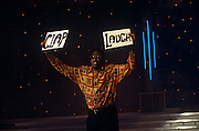 BBC warm-up man Miles Crawford holds up two boards prompting the audience watching the National Lottery Show to Clap or Laugh in BBC Television Centre in West London, England. Lit by studio lighting with a universe of stars in the background, Crawford is a respected and versatile stand-up comic and TV personality in his own right  working for the BBC, Sky, Channel 4 and ITV. Ironically, warm-ups perform a preliminary act before a TV show is recorded to literally warm an audience into non-spontaneous laughter to help a comedy's atmosphere - albeit with the help of prompt signs like these. The first National Lottery Live show was at 19:00 on Saturday 19 November 1994.