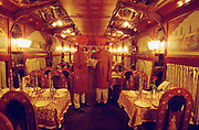 Stewards discussing the menue at the posh dining car of the Royal Orient.