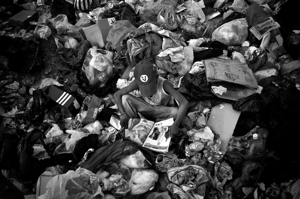 Avelio Naith, 10, in a red hat with the logo of the Venezuelan United Socialist party, reads a magazine at the Cambalache garbage dump in Ciudad Guayana, Venezuela. In an effort to escape poverty, hunger and to be closer to health care facilities, approximately 300 Warao indigenous persons from the Delta Amacuro have settled in Ciudad Guayana, in northeastern Venezuela. The Warao sustain themselves and their families by salvaging recyclables, clothing and discarded food in Cambalache, located minutes from downtown Ciudad Guayana. Although Warao community leaders say their quality of life is improved in comparison to the conditions in the Delta, the Warao are still plagued by hunger and diseases consequential of the unsanitary conditions of living in working in Cambalache.