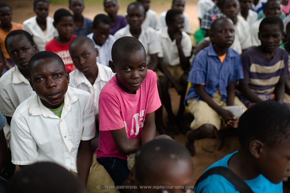"""Jacob Kisangala, wearing a Plan International """"Because I am a Girl"""" T-shirt, during a talk on menstrual hygiene management at Achilet Primary School near Tororo in Eastern Uganda on 1 August 2014. Education about menstruation is provided to both boys and girls to destigmatise it, and to improve the general level of knowledge about it in the community."""