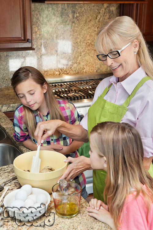 Senior woman with granddaughters mixing batter in kitchen