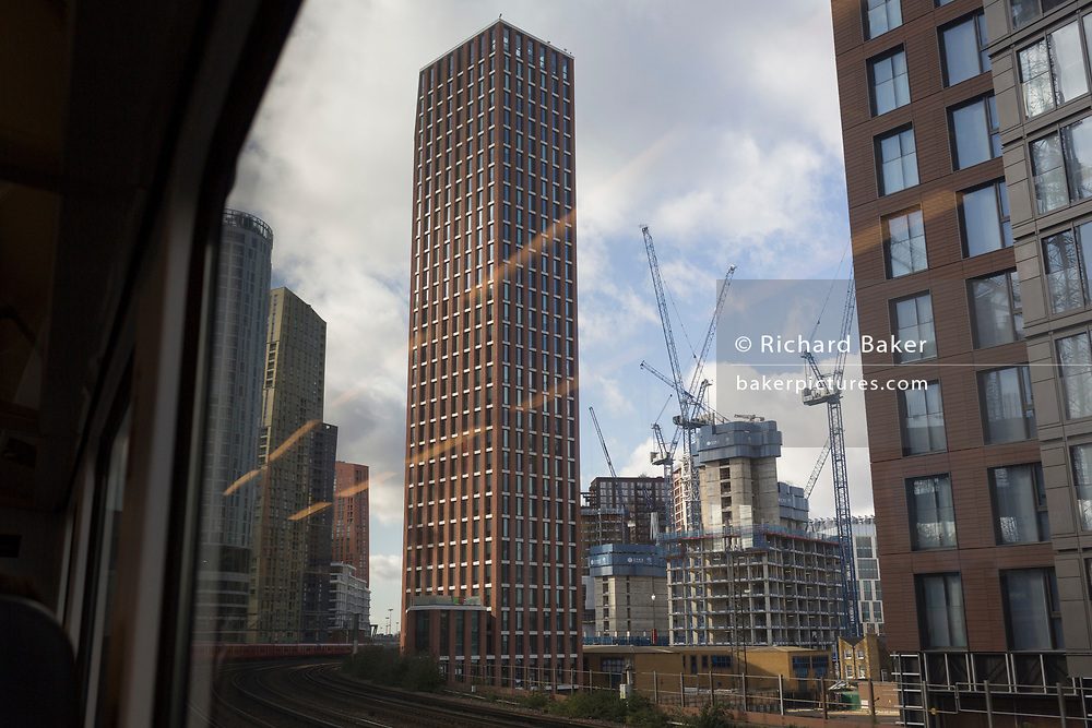 Trackside apartments and flats at the Nine Elms regeneration development in Battersea, seen through the window of a Southern train carriage window, on 7th November 2019, in London, England