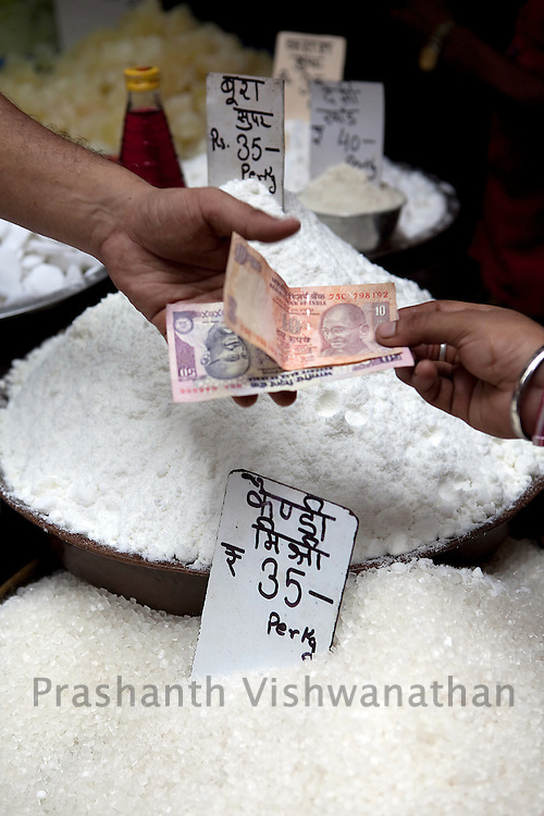 A customer pays for sugar, at a wholesale market in Old Delhi, in New Delhi, India, on Wednesday September 2, 2010. Photographer: Prashanth Vishwanathan/Bloomberg News