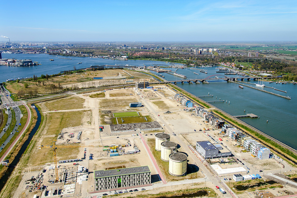 Nederland, Noord-Holland, Amsterdam, 20-04-2015; Zeeburgereiland met silo's van de voormalige rioolwaterzuivering Zeeburg en zelfbouwkavels. Foto richting Oranjesluizen en Schellingwouderbrug.<br /> Island Zeeburg, Amsterda East, former sewage treatment paltm and industrial ares, now new urban developement.<br /> <br /> luchtfoto (toeslag op standard tarieven);<br /> aerial photo (additional fee required);<br /> copyright foto/photo Siebe Swart