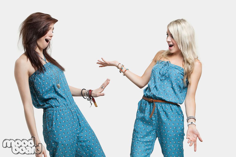Two surprised women wearing similar jump suits looking at each other over gray background