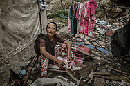 """Sara is among the poorest of the poor in Market 3 slum.  Her husband, """"Kulot"""", was a victim of an extrajudicial killing because he was a known user of """"shabu"""" (methampetamine).  Because Sara is completely destitute, Kulot's embalmed body lay for over 25 days in the morgue before finally being interred in a mass grave.  She lived in this canvas hut (left) until it was burned down.  Now she sleeps in a chicken coop.  Market 3 slum, Navotas.  Metro Manila, Philippines"""